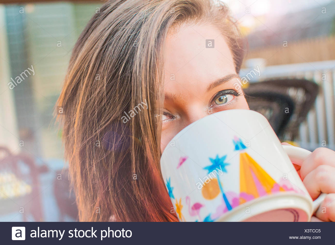 Close up of young woman drinking coffee from mug - Stock Image