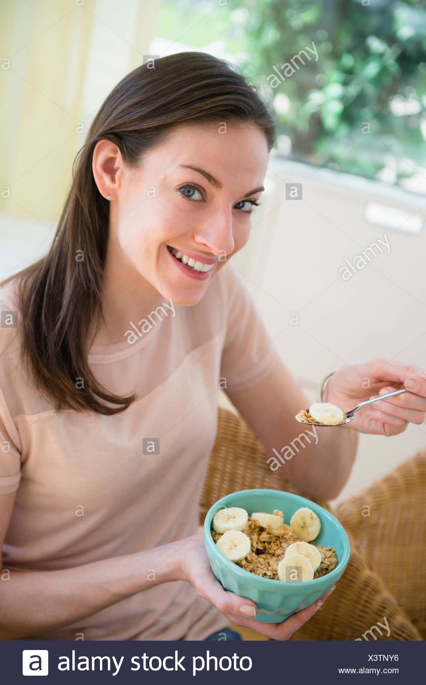 Woman at home eating healthy breakfast - Stock Image