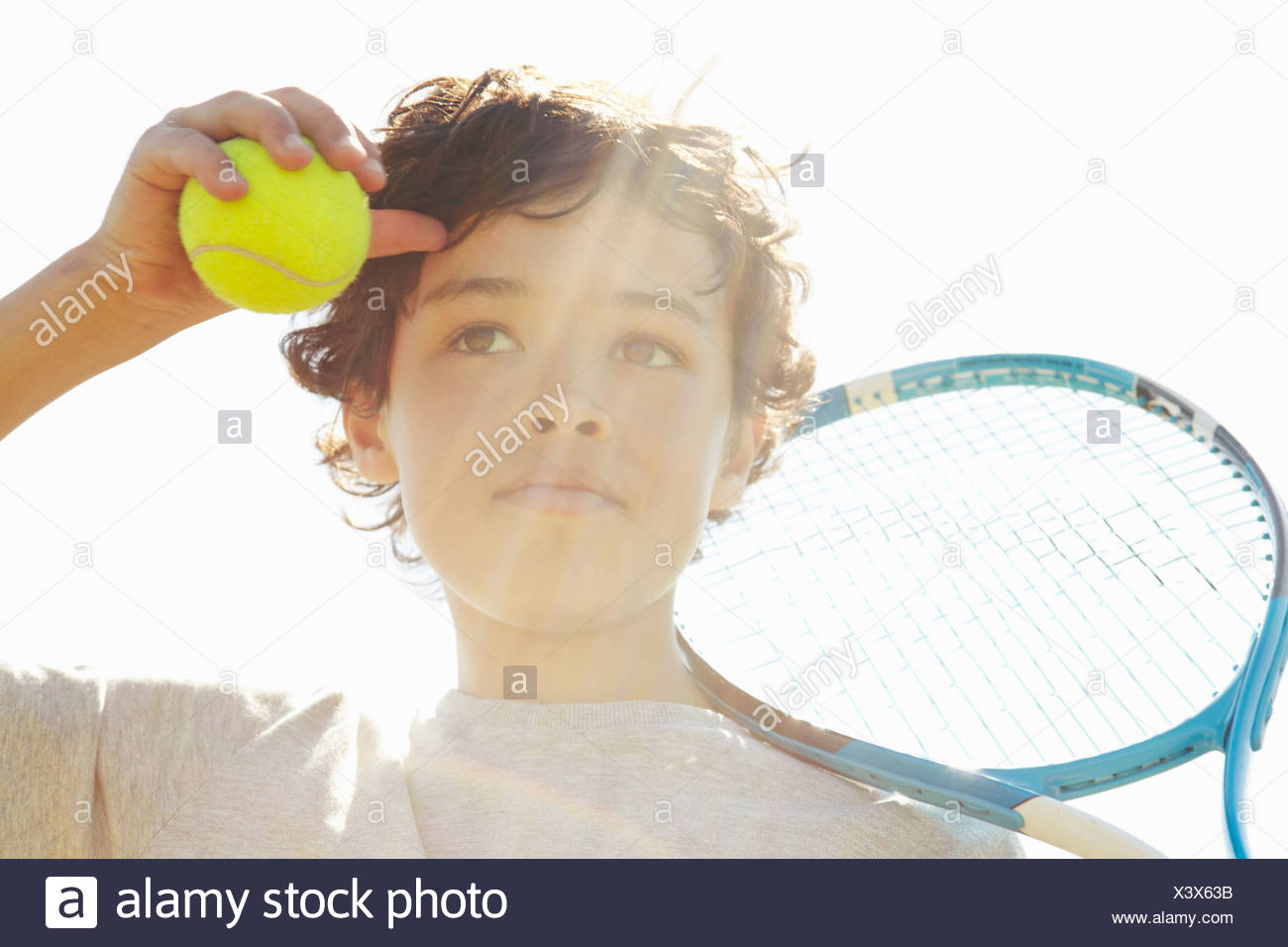 Close up of boy with tennis racket and ball - Stock Image