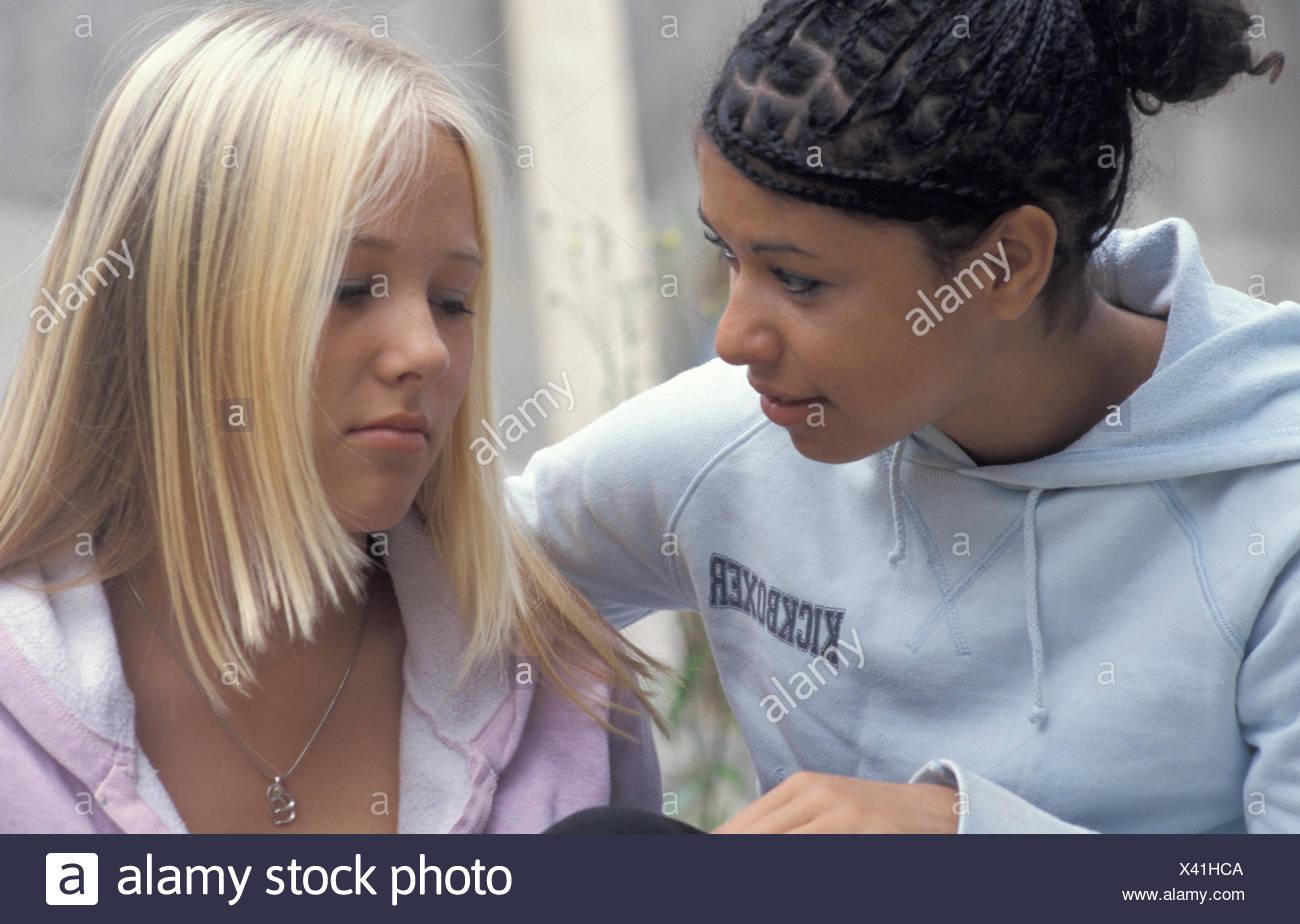 teenage girl talking to her moody friend - Stock Image
