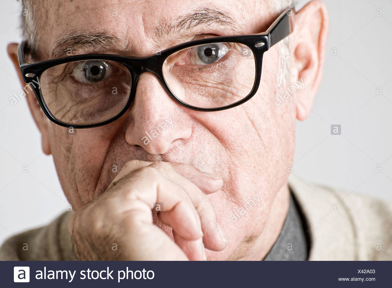 Portrait of senior man, hand on mouth - Stock Image