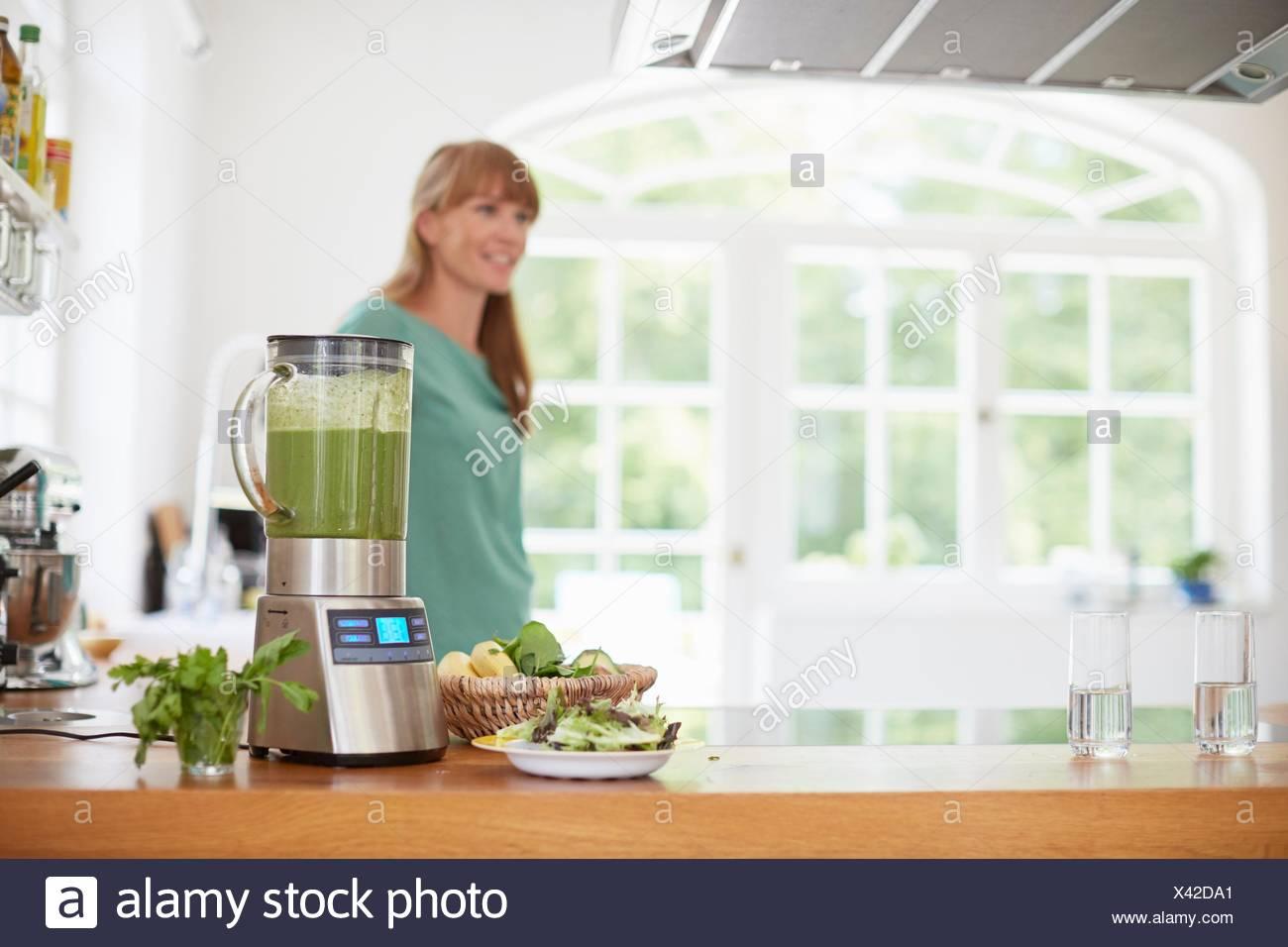 Woman next to blender full of green vegan smoothie - Stock Image