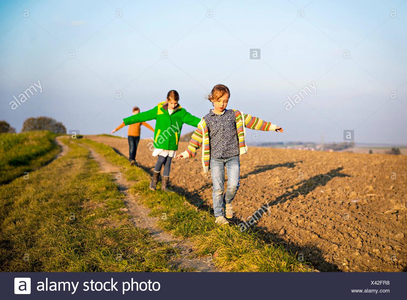 Three children playing outdoors - Stock Image