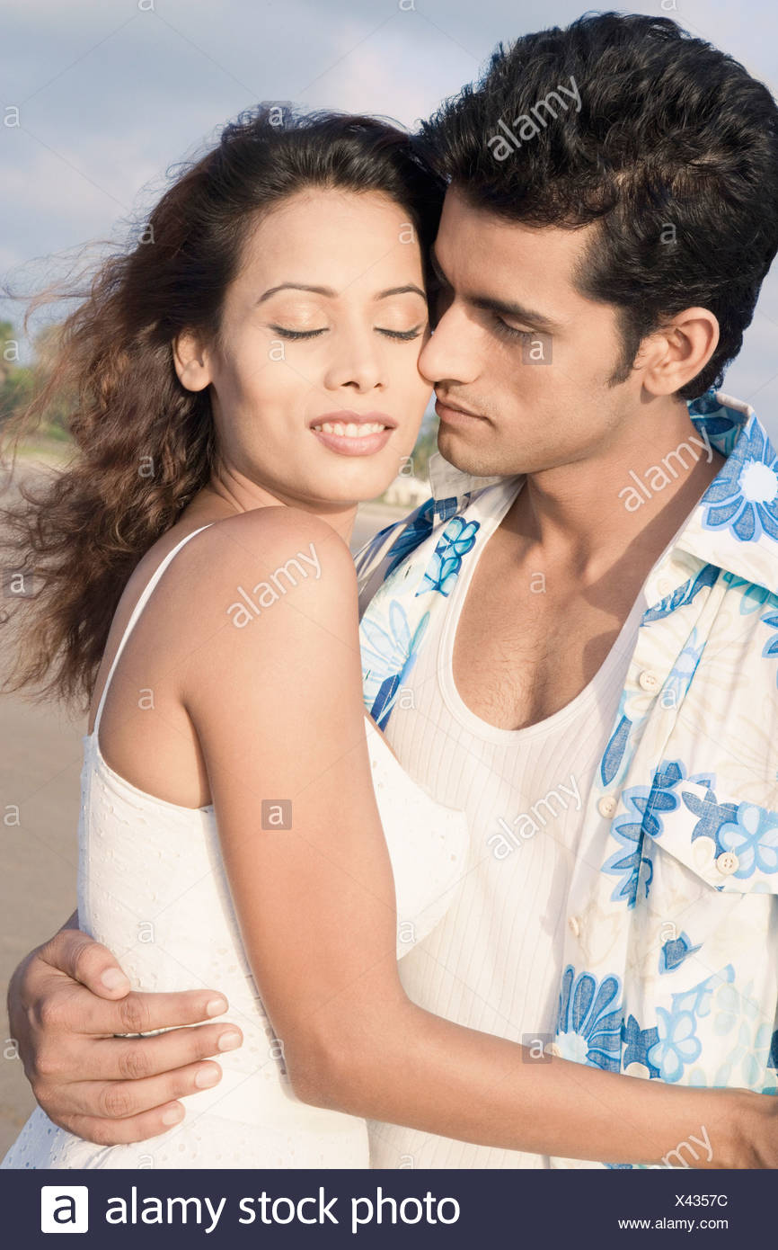 close up of a young couple romancing on the beach stock photo