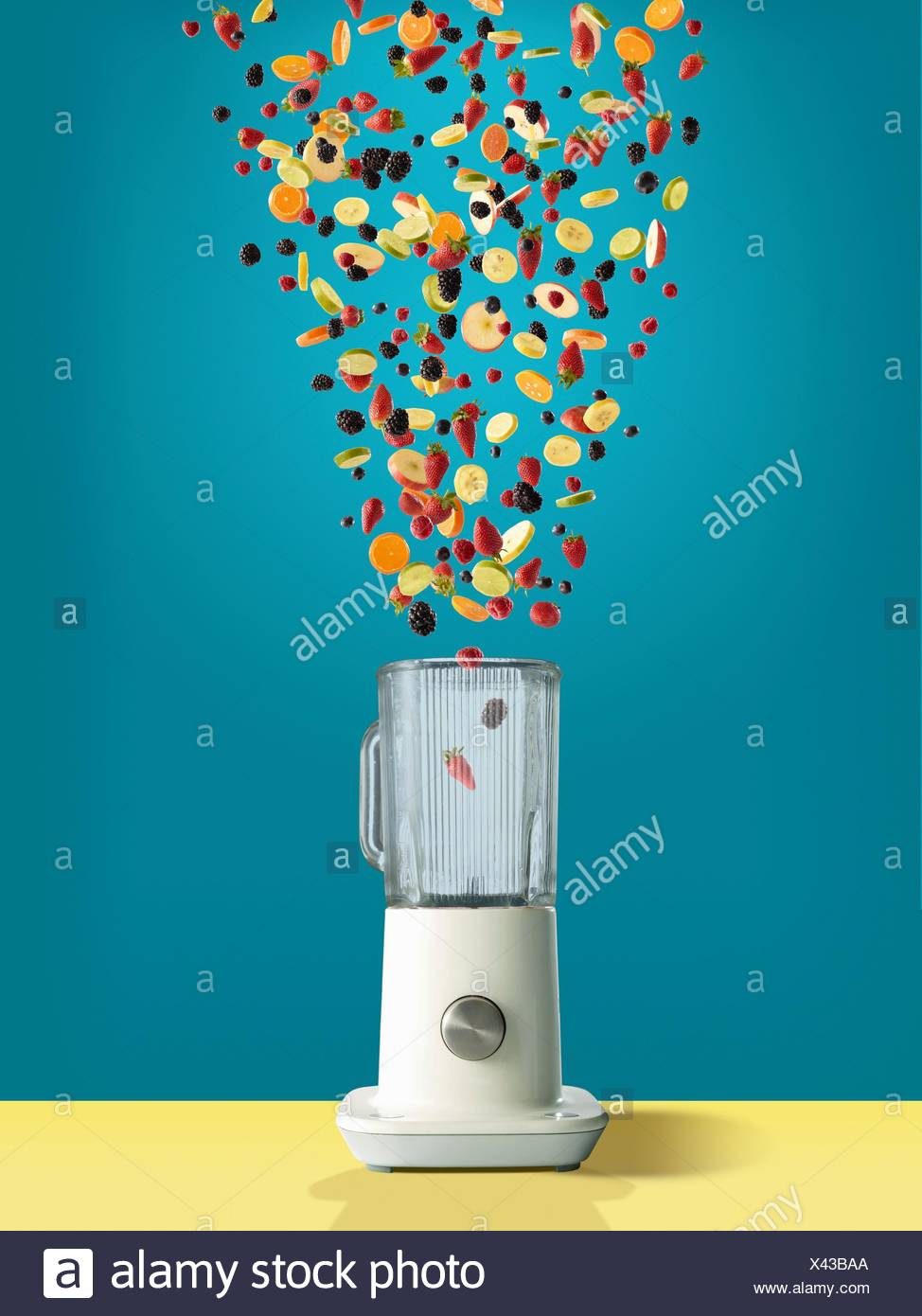 Variety of fresh sliced fruit and berries dropping into juicer - Stock Image