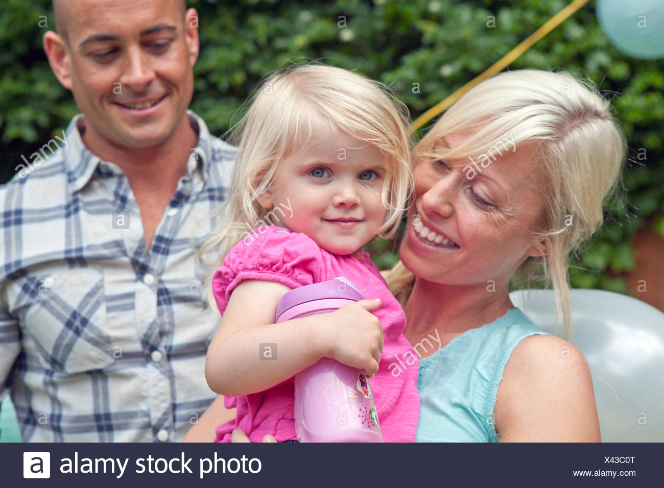 Happy mother and father with toddler daughter - Stock Image