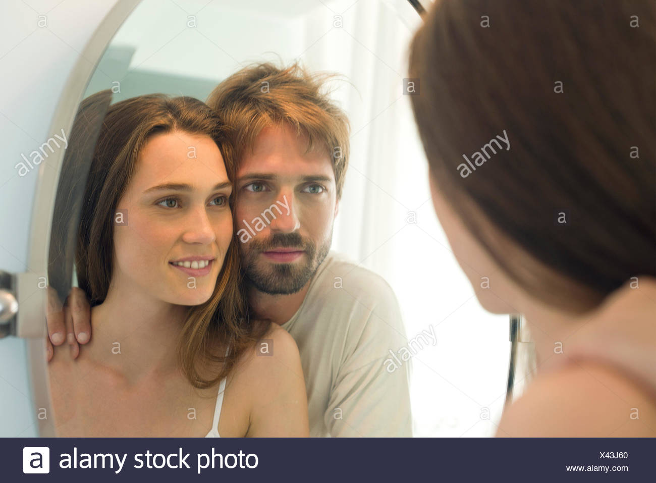 Couple looking in bathroom mirror together - Stock Image