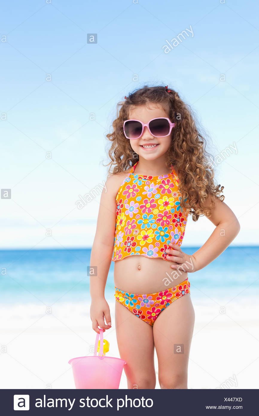 fb27659d00461 Cute little girl with sunglasses standing on the beach Stock Photo ...