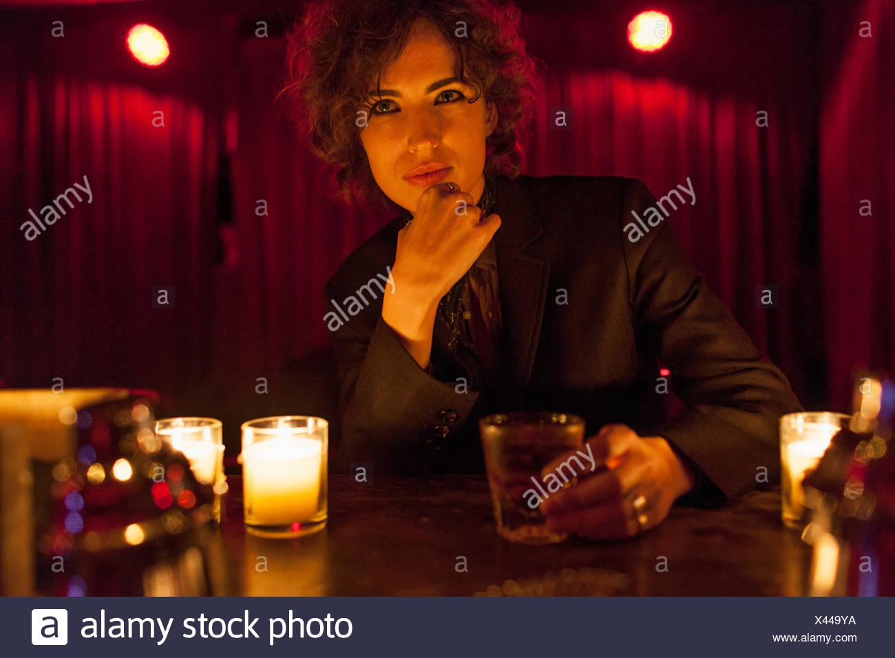 Woman enjoying a drink at a bar - Stock Image