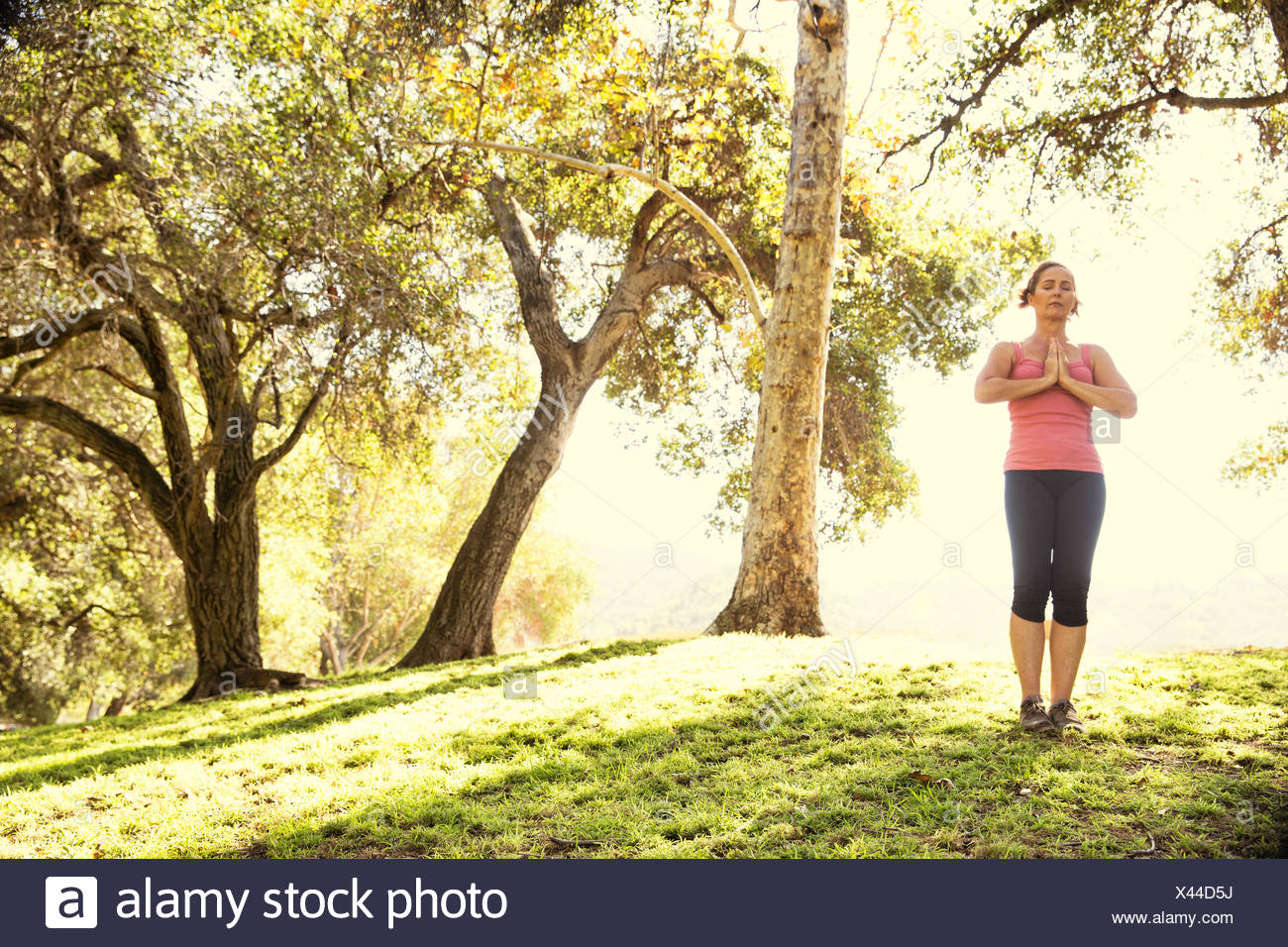 Mature woman in park practicing yoga - Stock Image