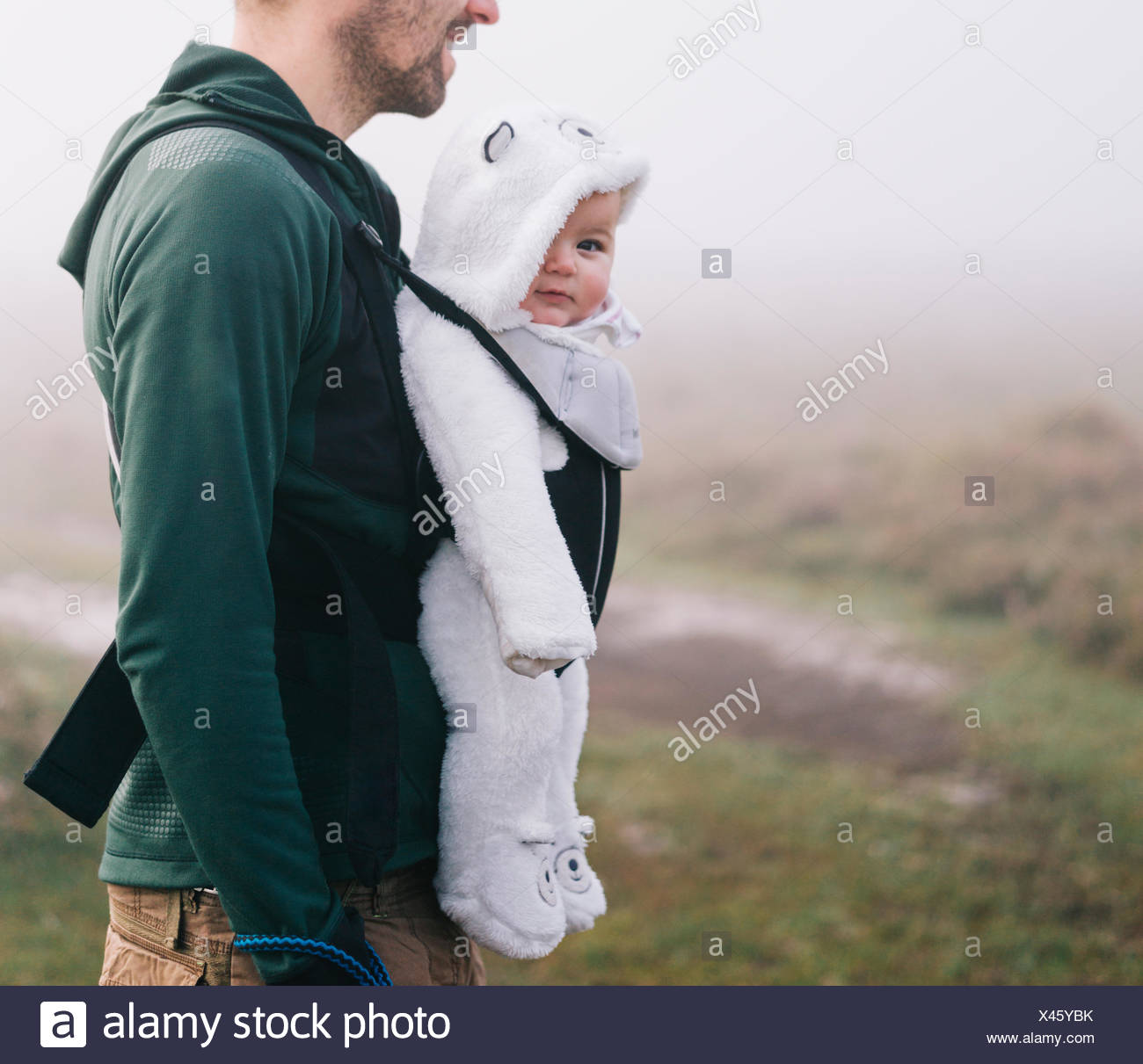 A man carrying a baby in a baby carrier on his chest, outdoors on a misty autumn day - Stock Image