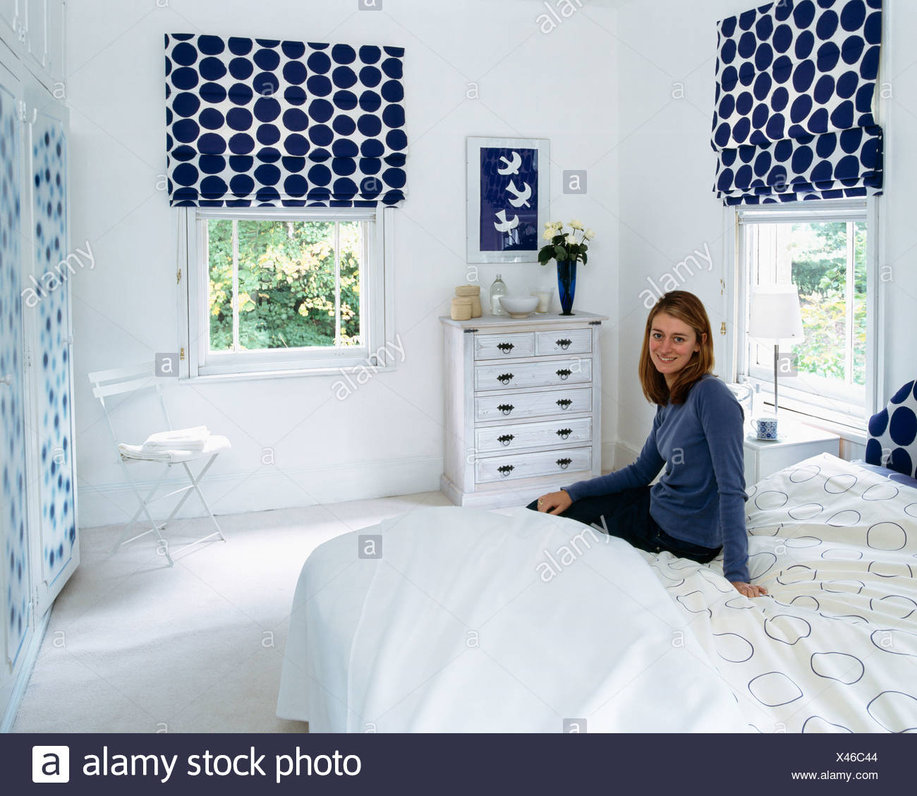 Young Woman Sitting On Bed In White Bedroom With Blue Spotted Blinds On  Windows