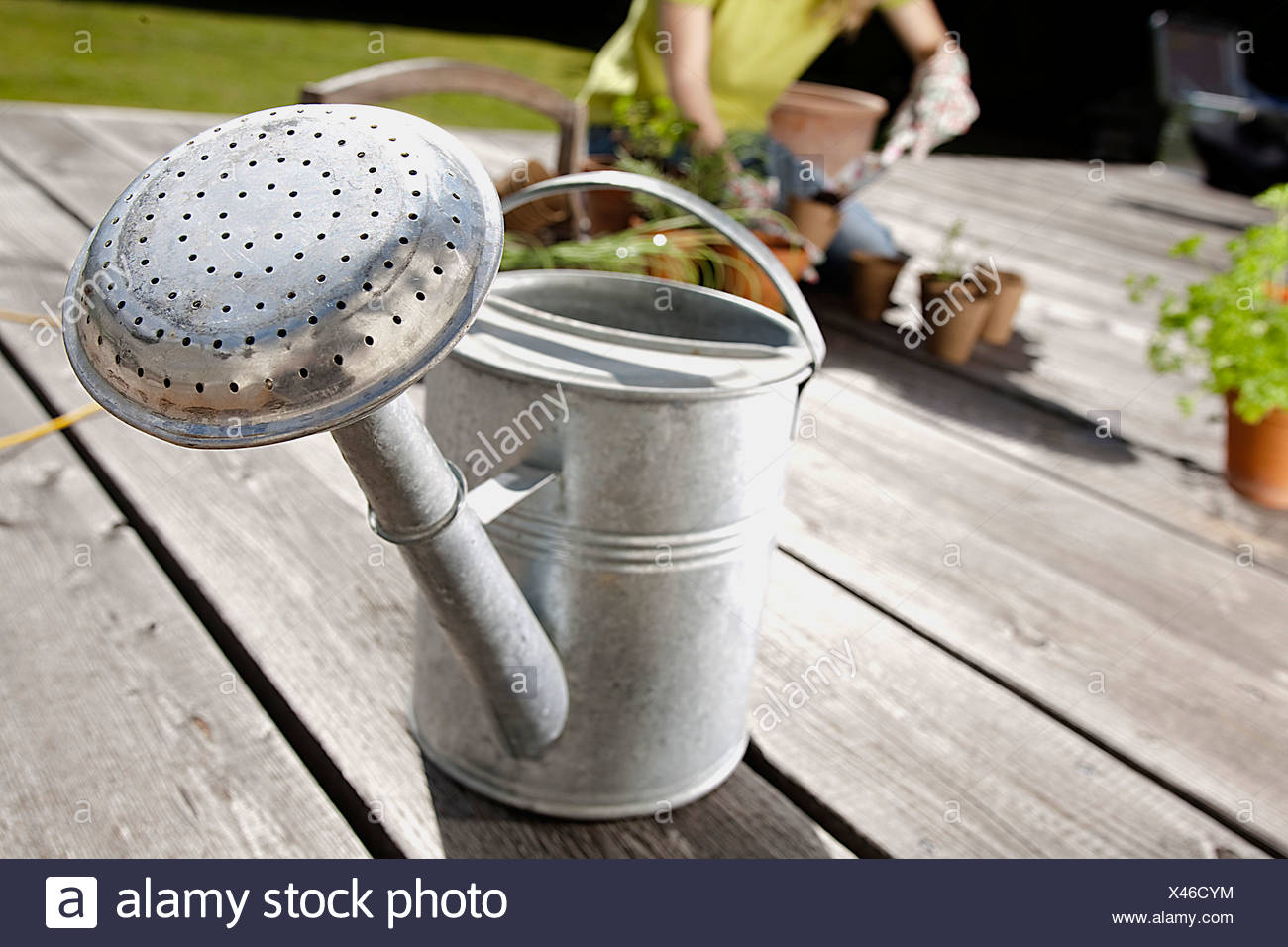 silver watering can on veranda - Stock Image