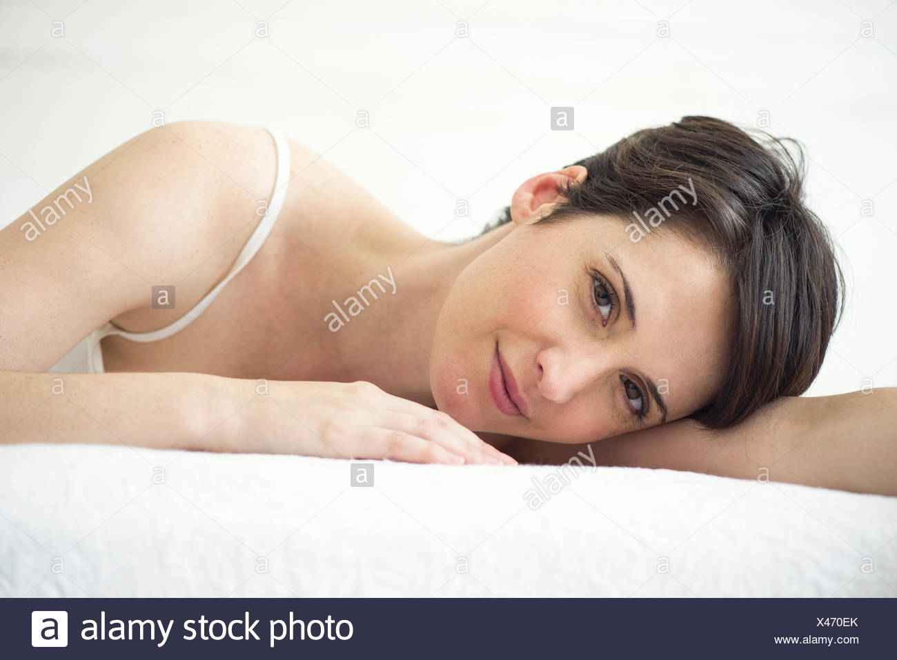Woman resting on bed, portrait - Stock Image