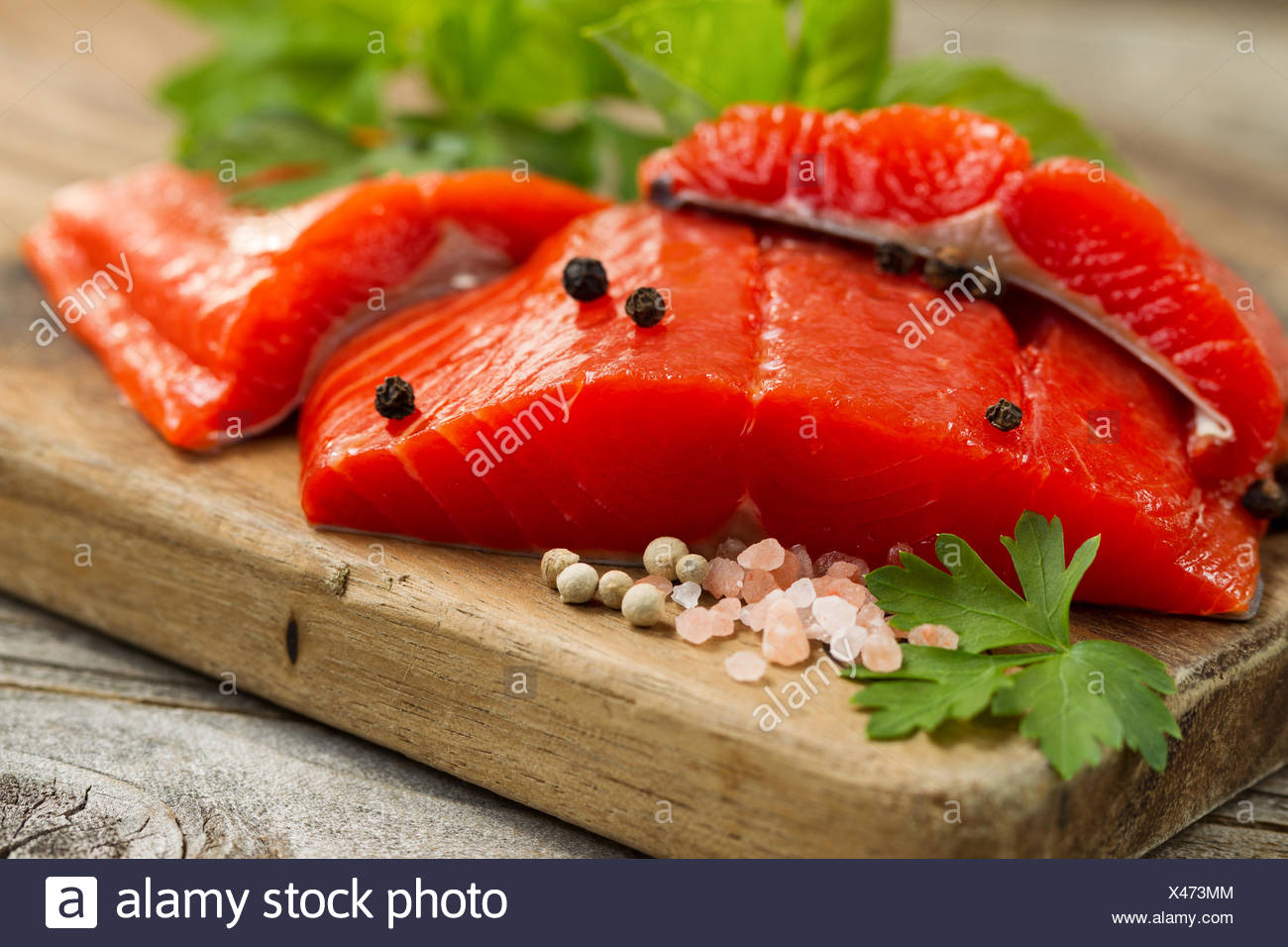 Fresh Copper River Salmon fillets on rustic wooden server with spices and herbs - Stock Image