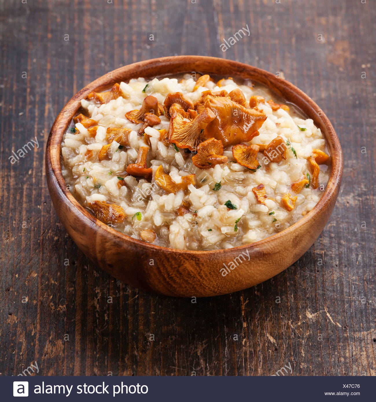 Risotto with chanterelles in wooden bowl - Stock Image