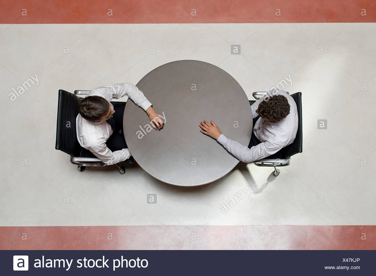 Businessmen stting opposite each other - Stock Image