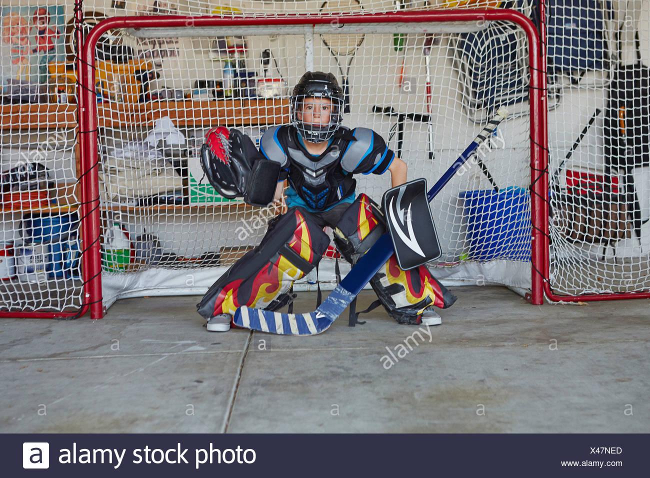 Boy in hockey goal wearing protective sportswear - Stock Image