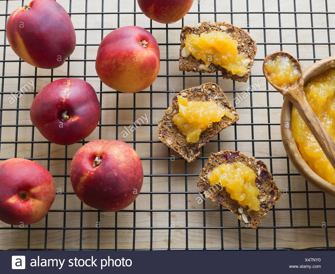 Fresh peaches and peach spread on almond crisps - Stock Image