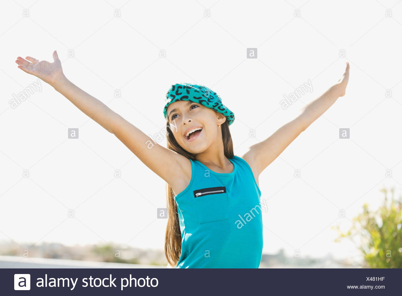 Girl with arms raised outdoors - Stock Image