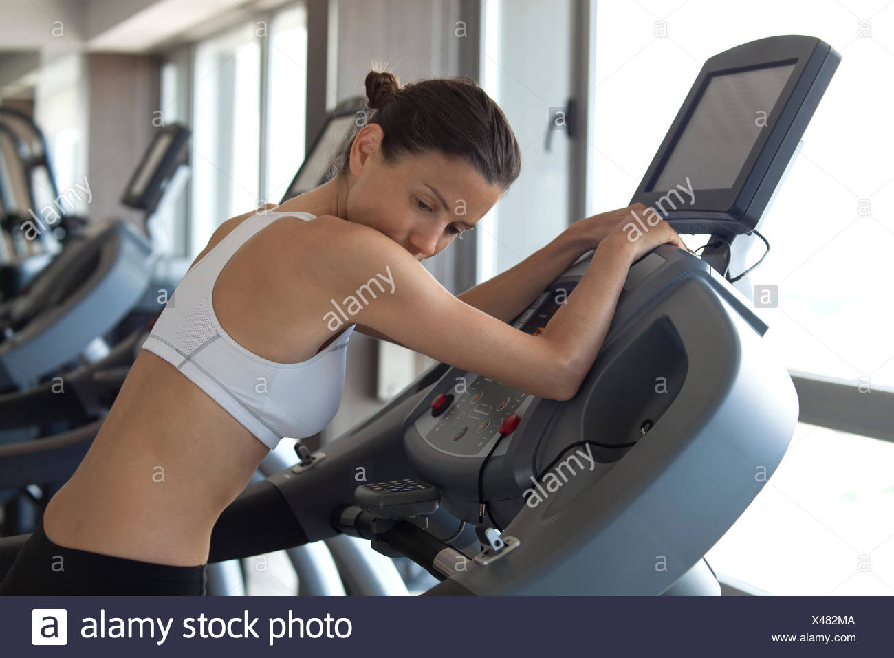 Woman using exercise machine in health club - Stock Image
