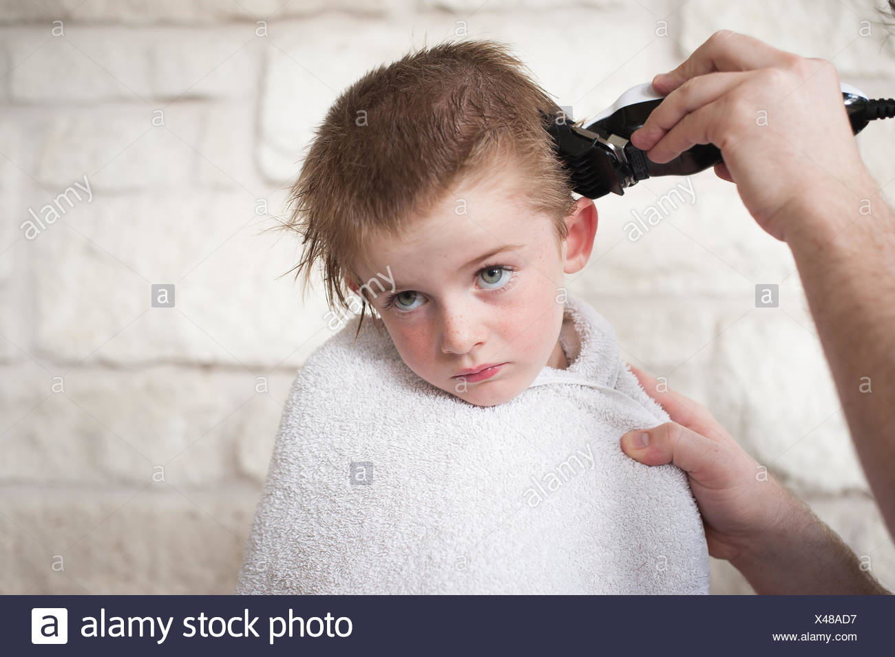 Boy getting a buzz hair cut by his father - Stock Image