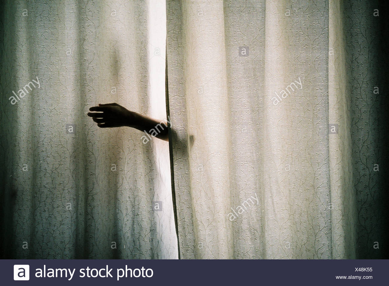 Hand reaching from behind curtain - Stock Image