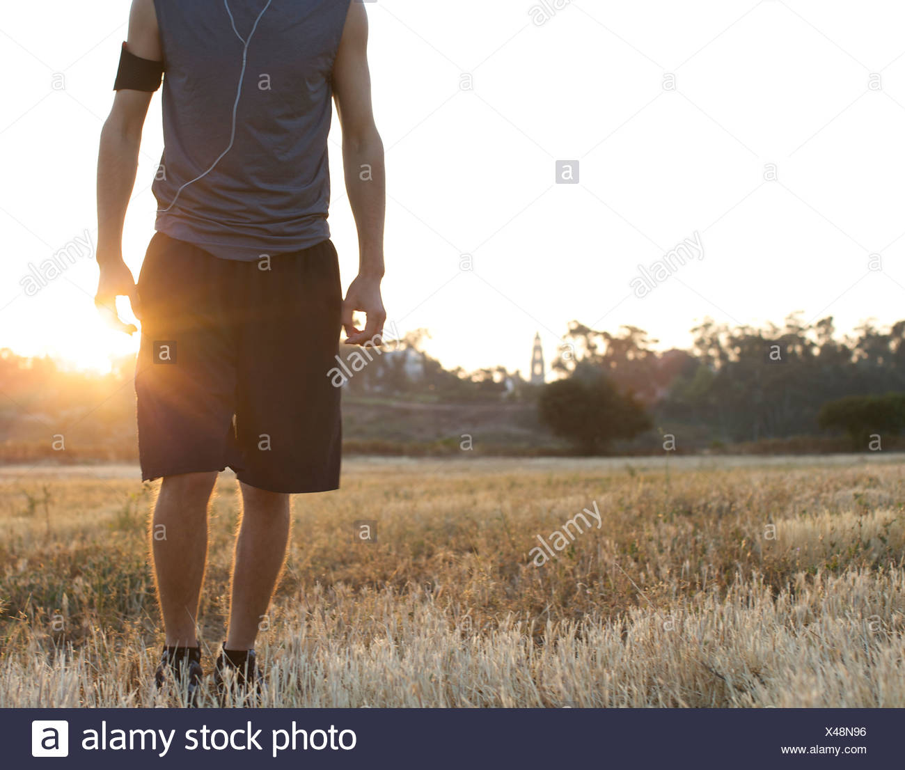 Male runner stays still for a portrait at an open field with backlight in San Diego, California. - Stock Image
