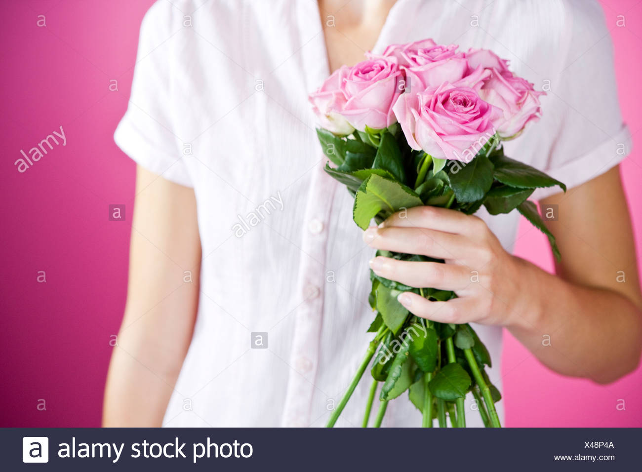 A Young Woman Holding A Bunch Of Pink Roses - Stock Image