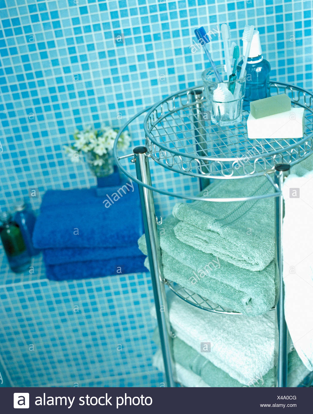 Close-up of folded towels on chrome shelf unit with glass shelves ...