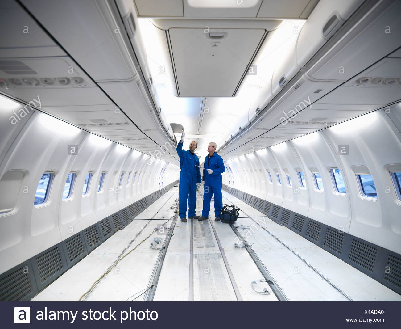 Worker examining empty airplane - Stock Image