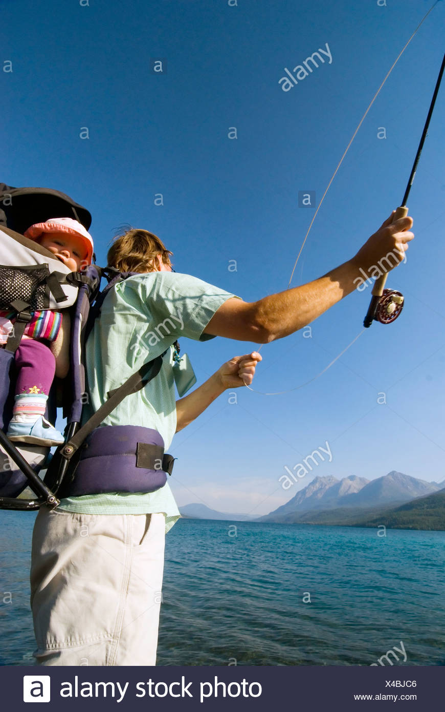 Fisherman father with daughter in child-carrier backpack, fly-fishing for trout, Tatlayoko Lake, British Columbia, Canada. - Stock Image