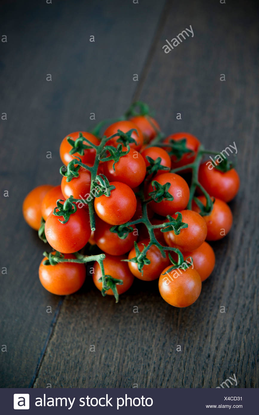 Cherry tomatoes on a dark wooden board - Stock Image