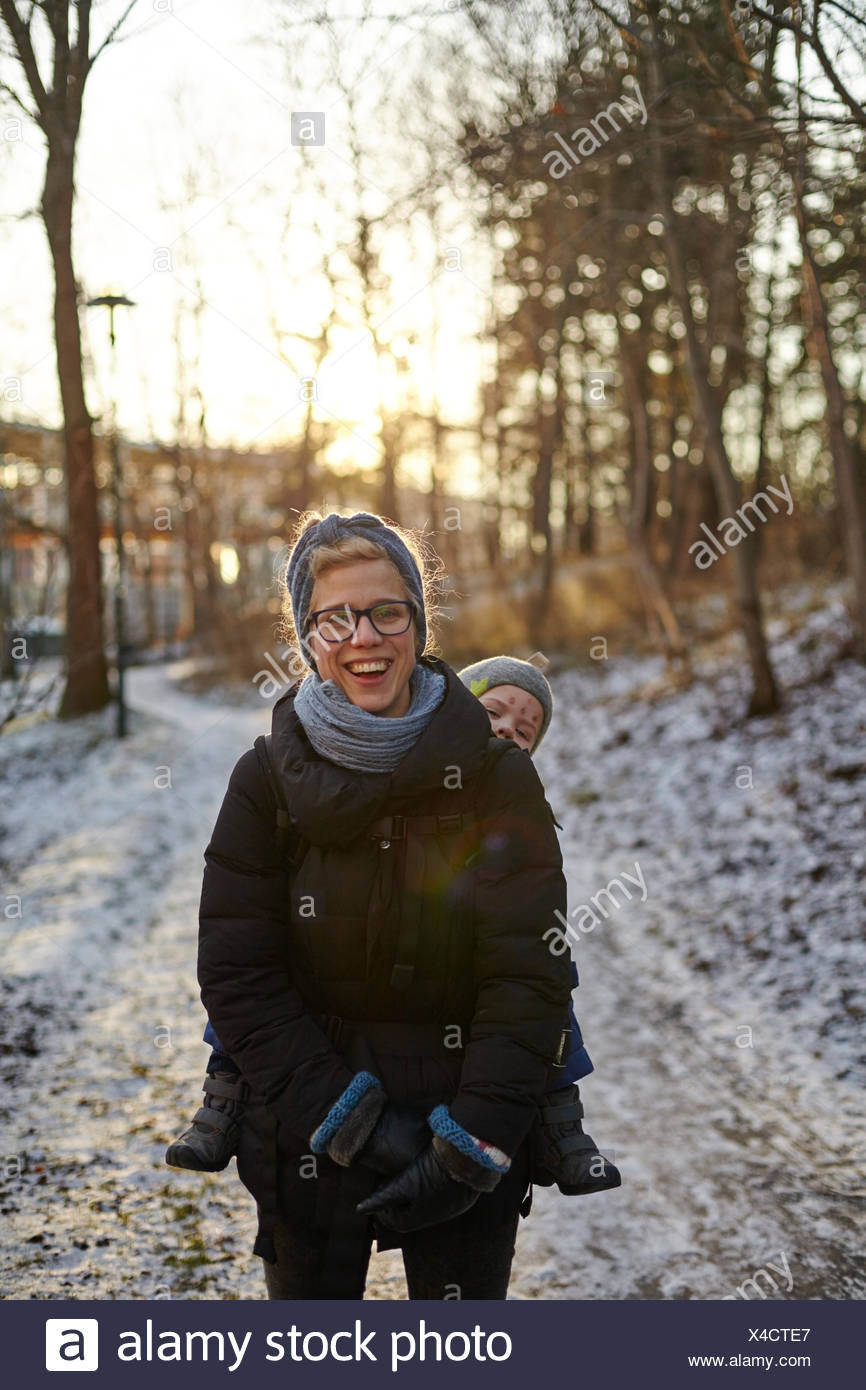 Sweden, Sodermanland, Stockholm, Johanneshov, Hammarbyhojden, Laughing mid adult woman carrying son (2-3) - Stock Image