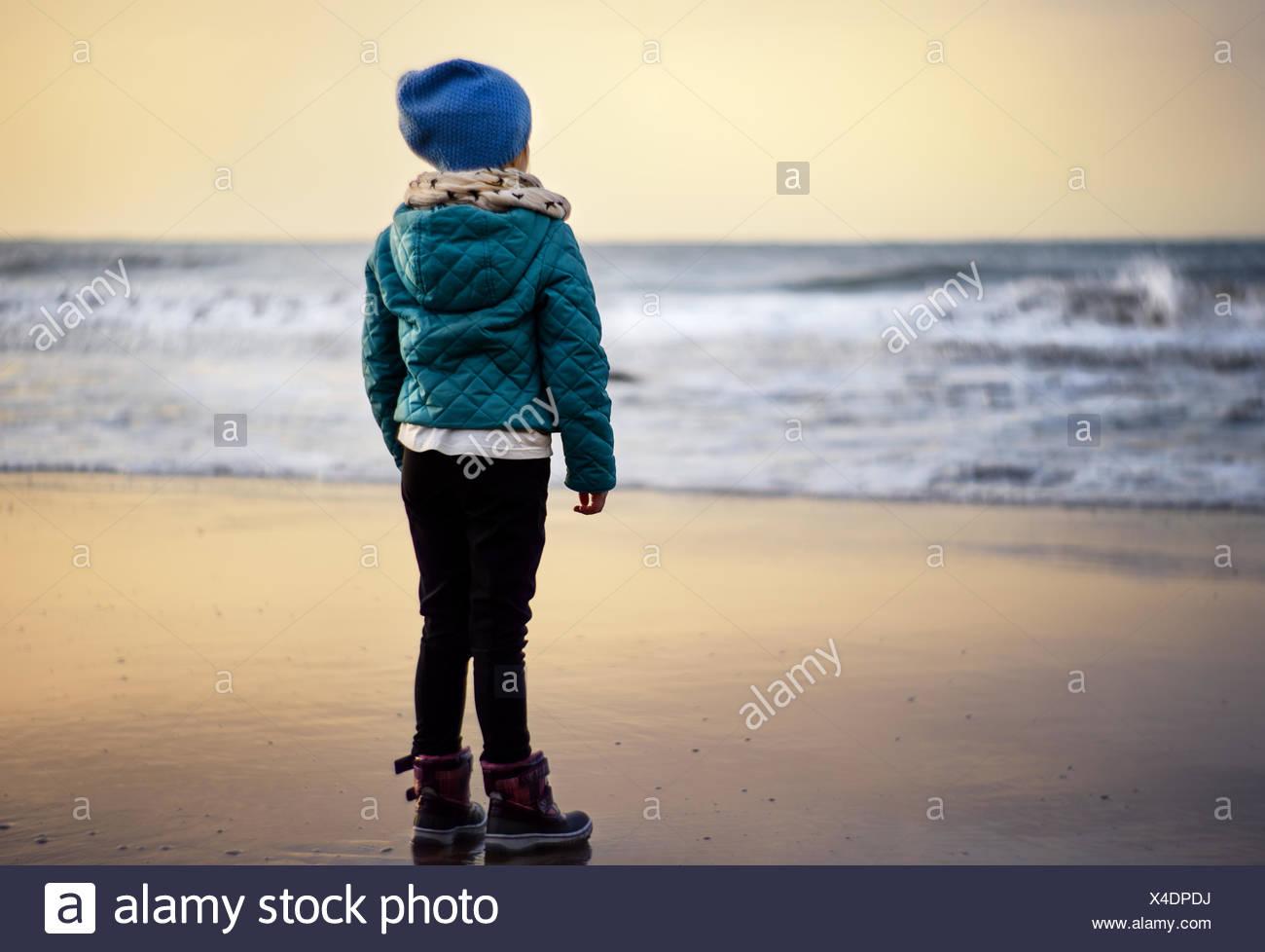 Girl (2-3) looking at beach at sunset - Stock Image