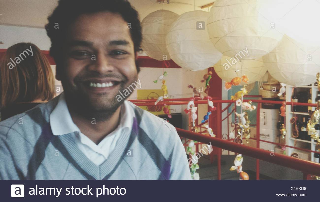 Smiling Mid Adult Man Standing By Lanterns - Stock Image