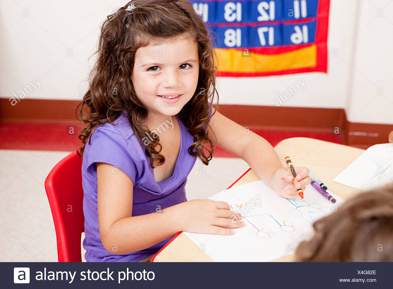 Girl drawing a picture in class - Stock Image