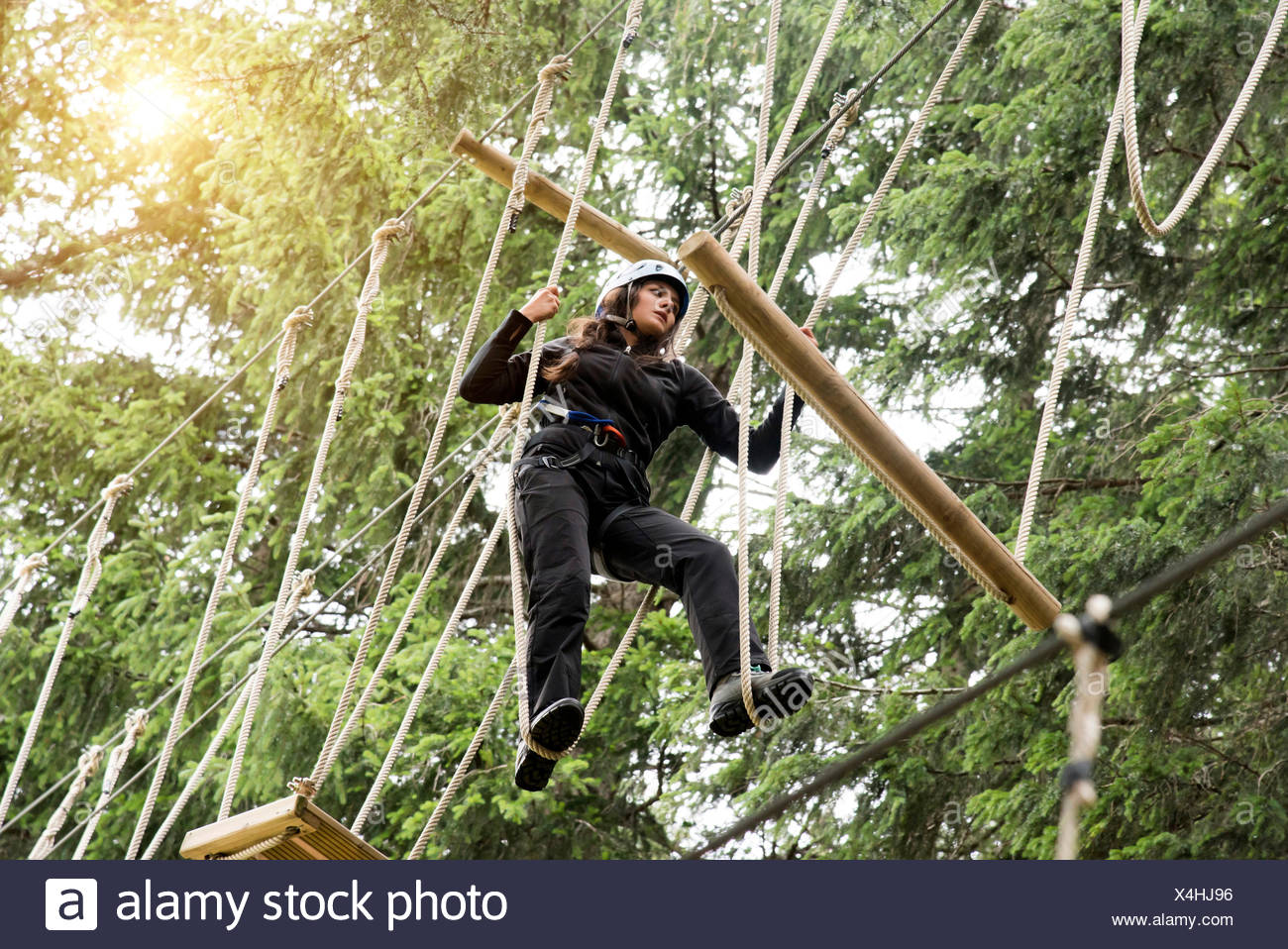 Teenage girl on high rope course - Stock Image
