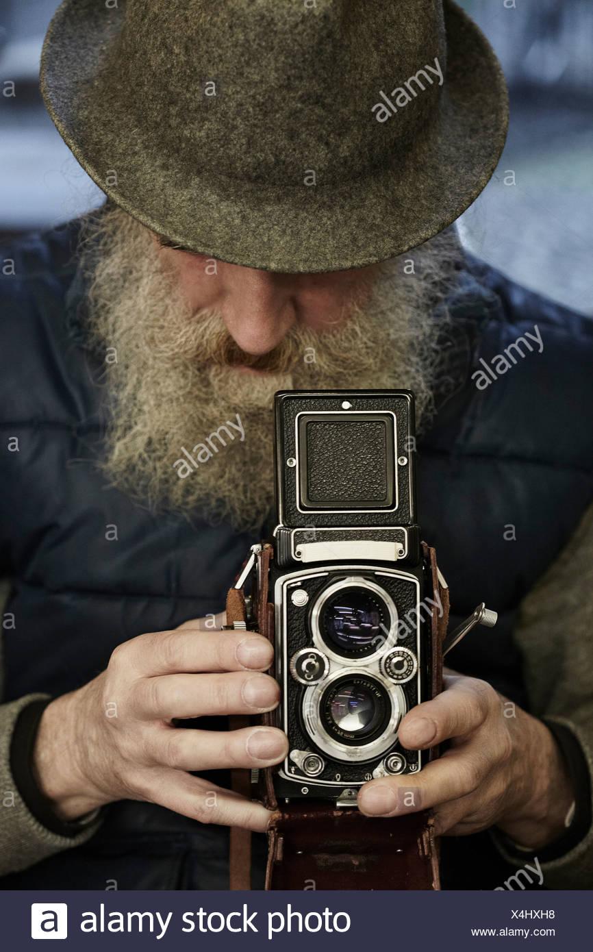 Senior man using twin lens reflex camera, close up - Stock Image