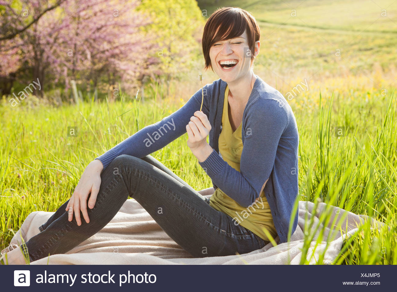 A young woman sitting in an open space, a grass field, on a blanket. - Stock Image