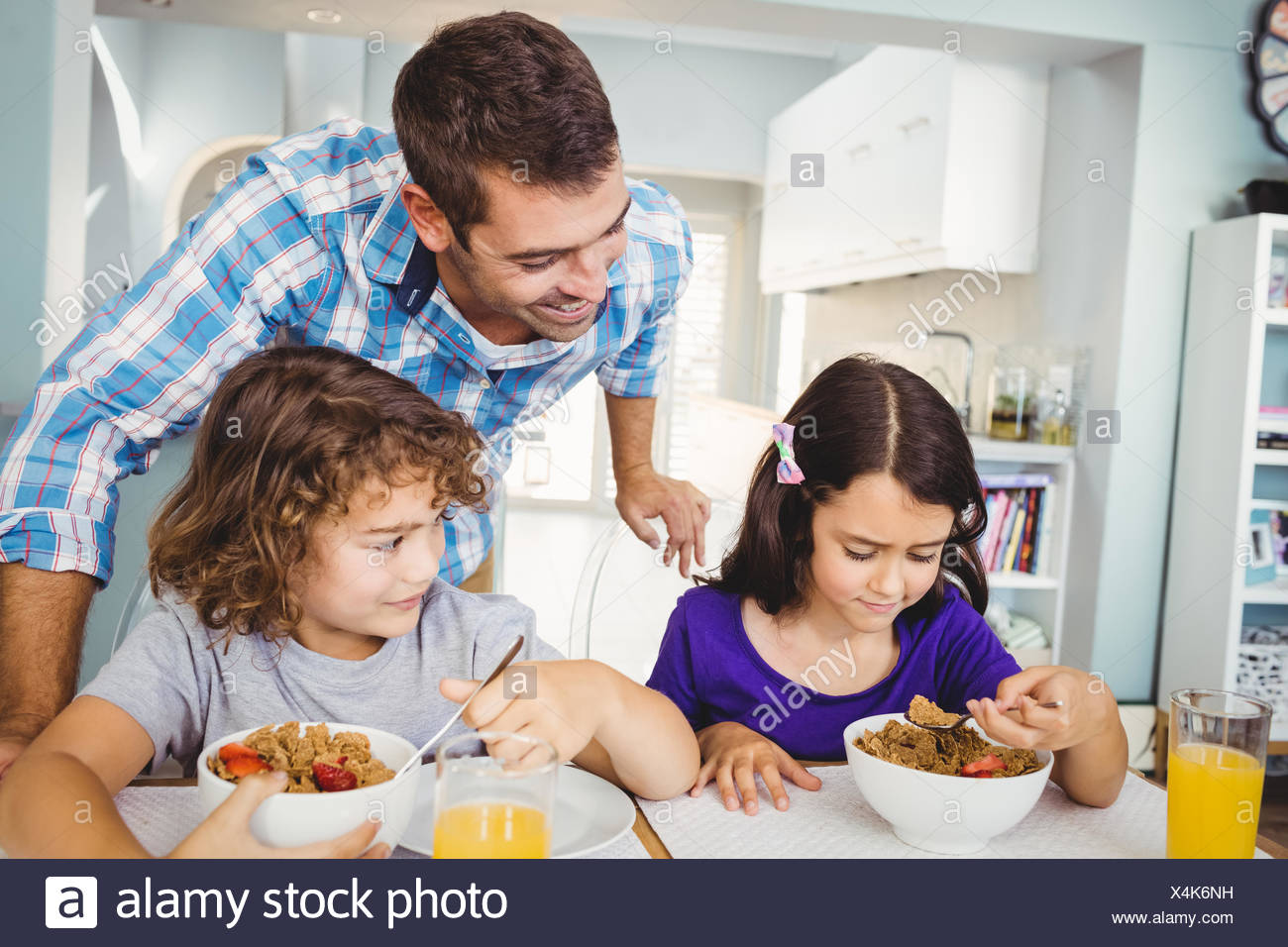 Cheerful man with children having breakfast - Stock Image