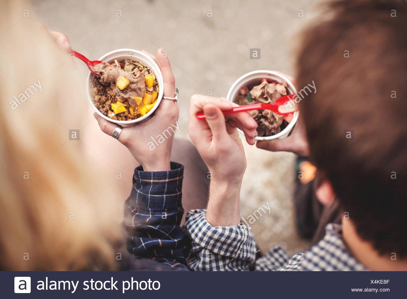 Couple eating tubs of frozen yoghurt treat - Stock Image