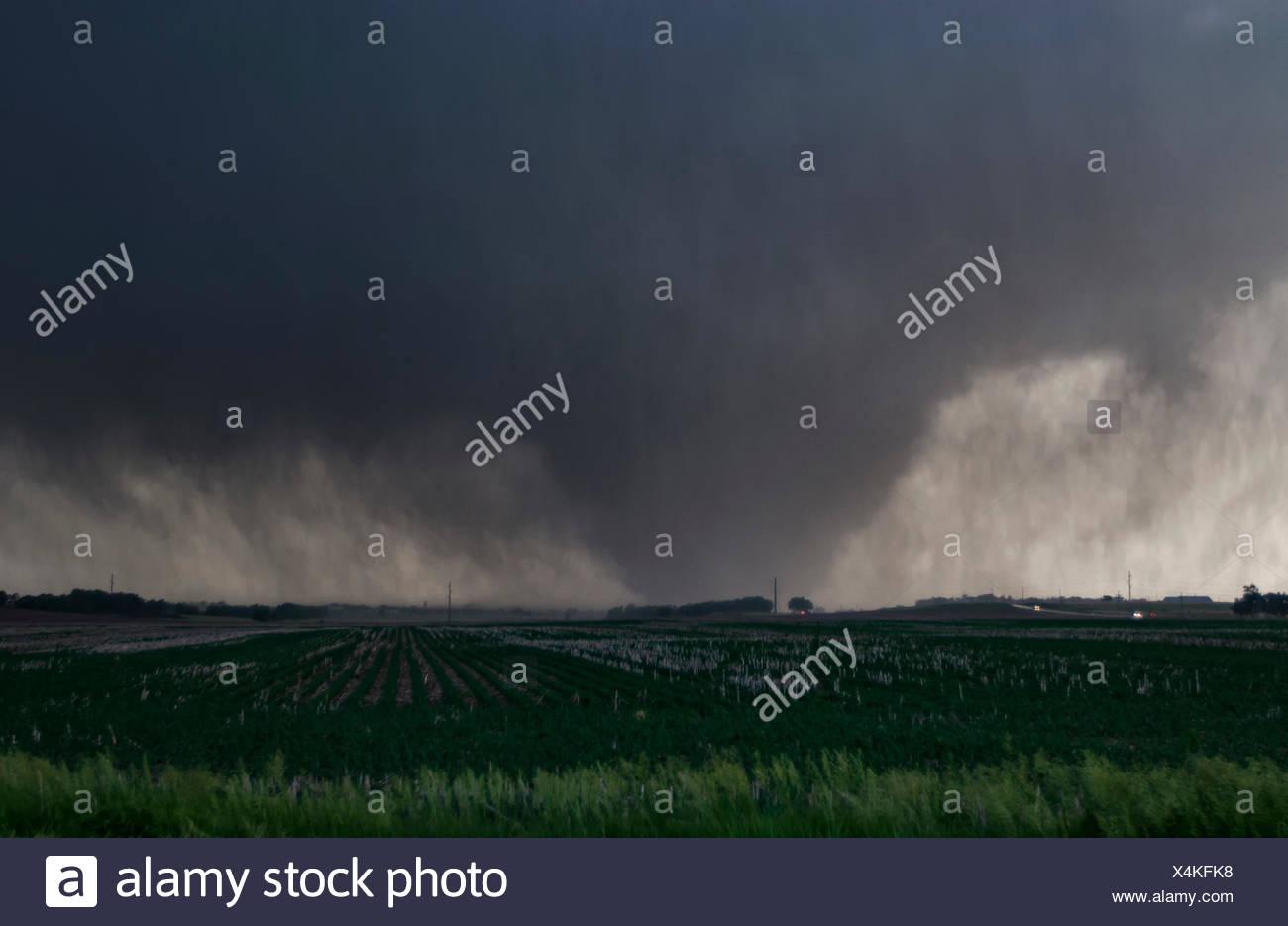 A violent, rain-wrapped wedge tornado rips up farmland in rural Kansas - Stock Image