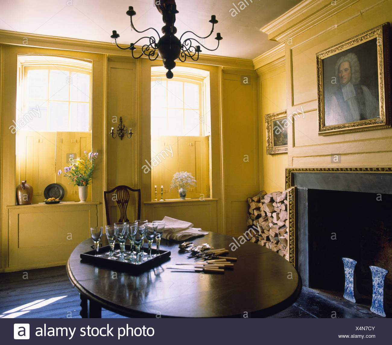 Antique Glasses On Polished Wooden Table In Yellow Georgian Dining Room With Shutters At The Windows