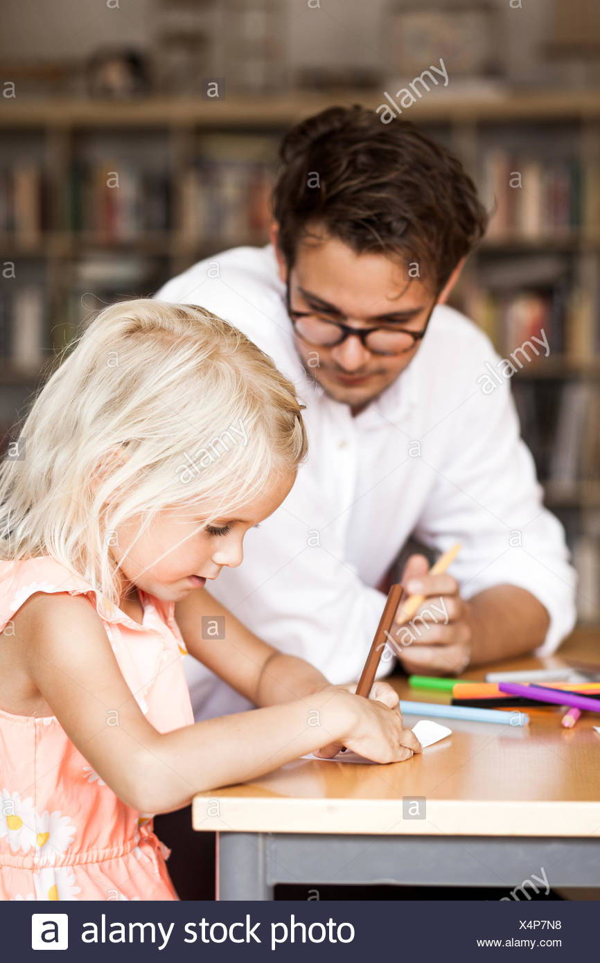 Male teacher watching girl drawing in class - Stock Image