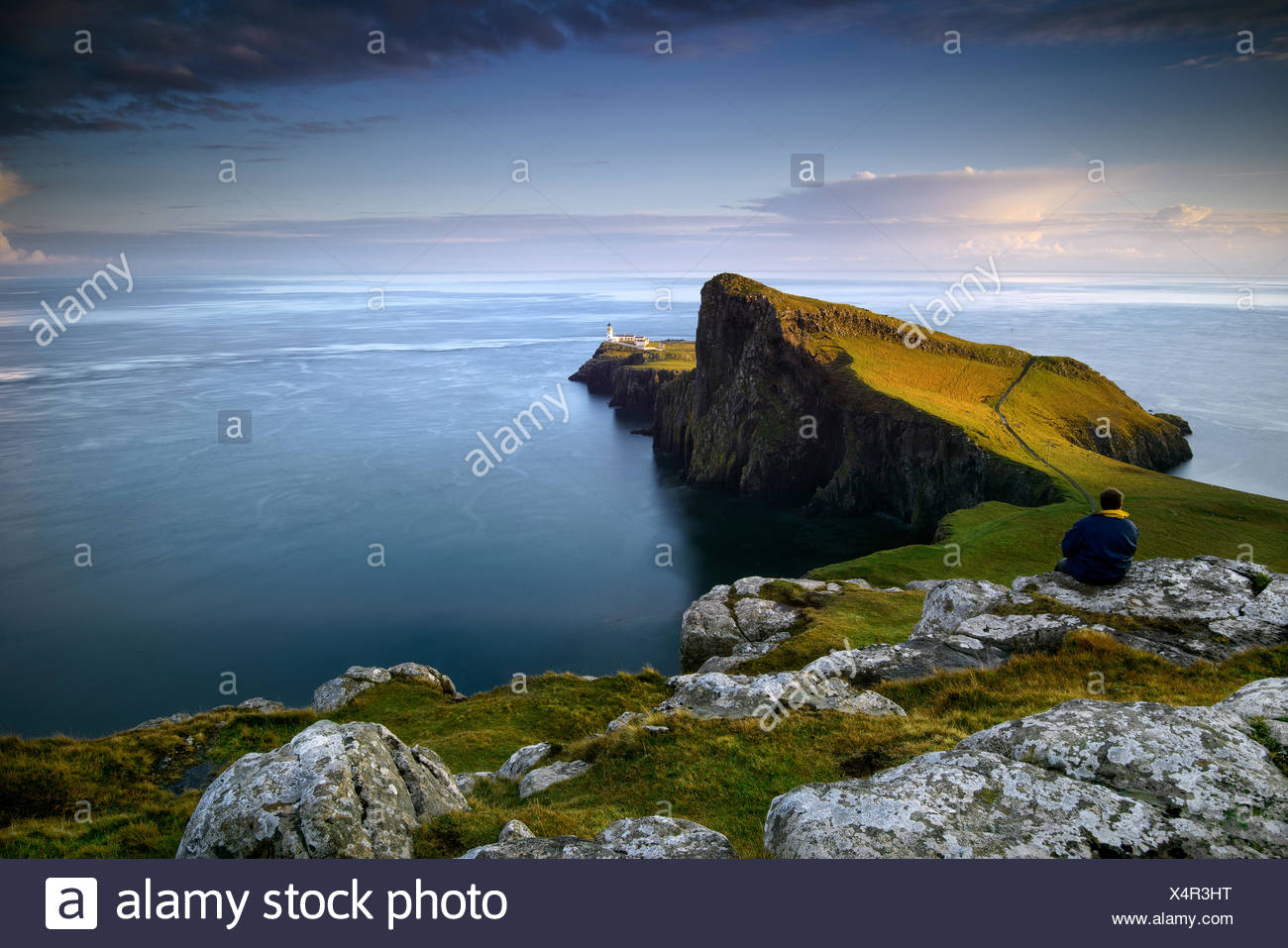 Mid adult man sitting on a rock looking out to sea at Neist Point, Scotland - Stock Image