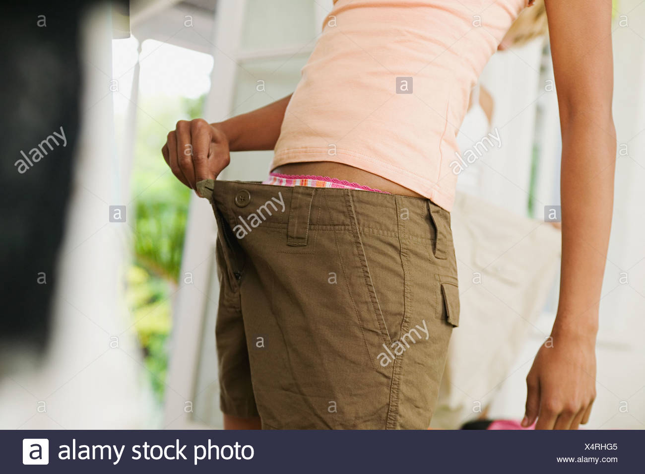 Woman wearing too large trousers - Stock Image