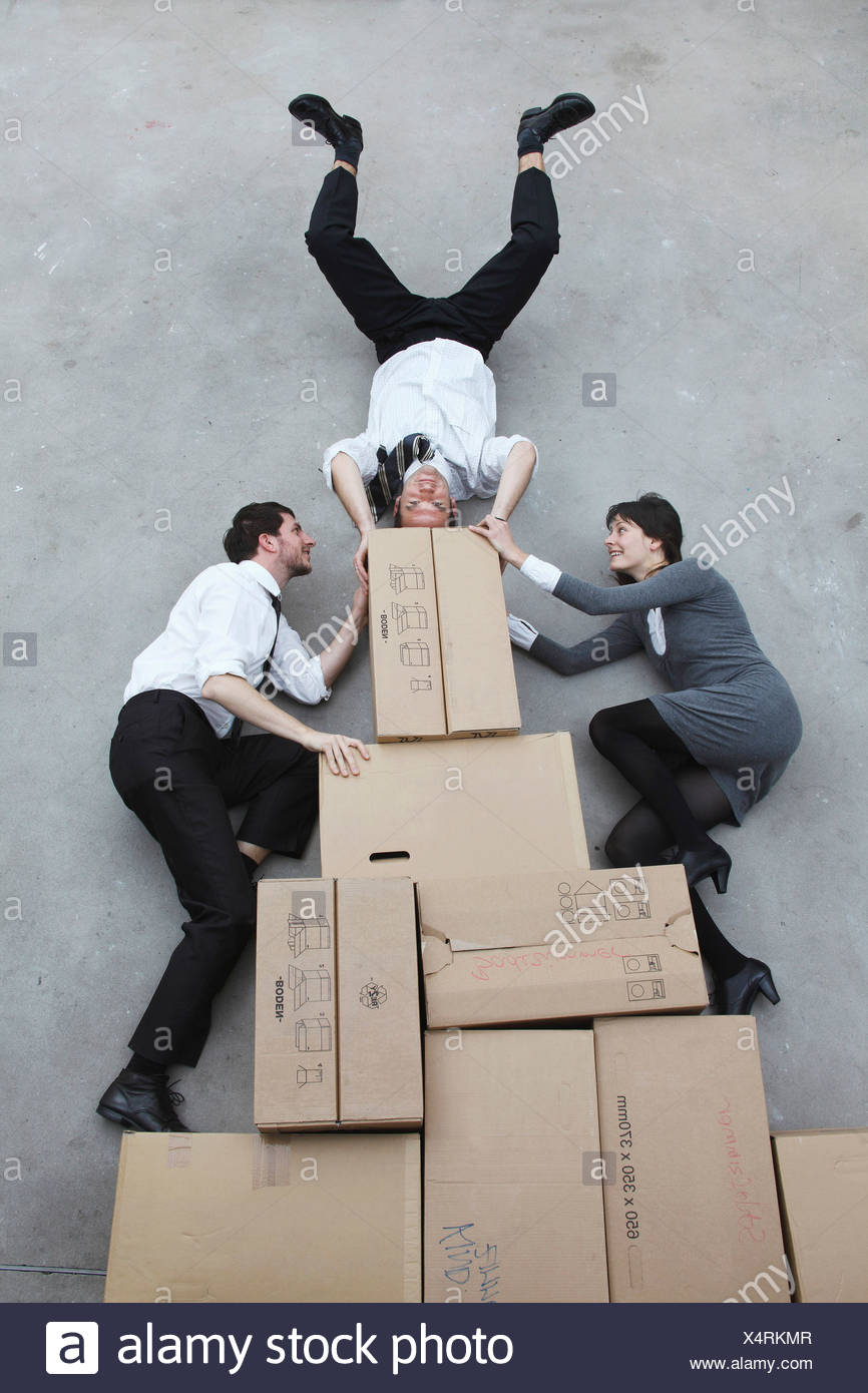 Three business people on cardboard boxes, man doing handstand, smiling, portrait, elevated view - Stock Image