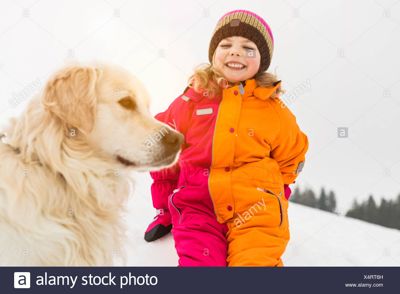 Girl wearing winter clothing with dog - Stock Image