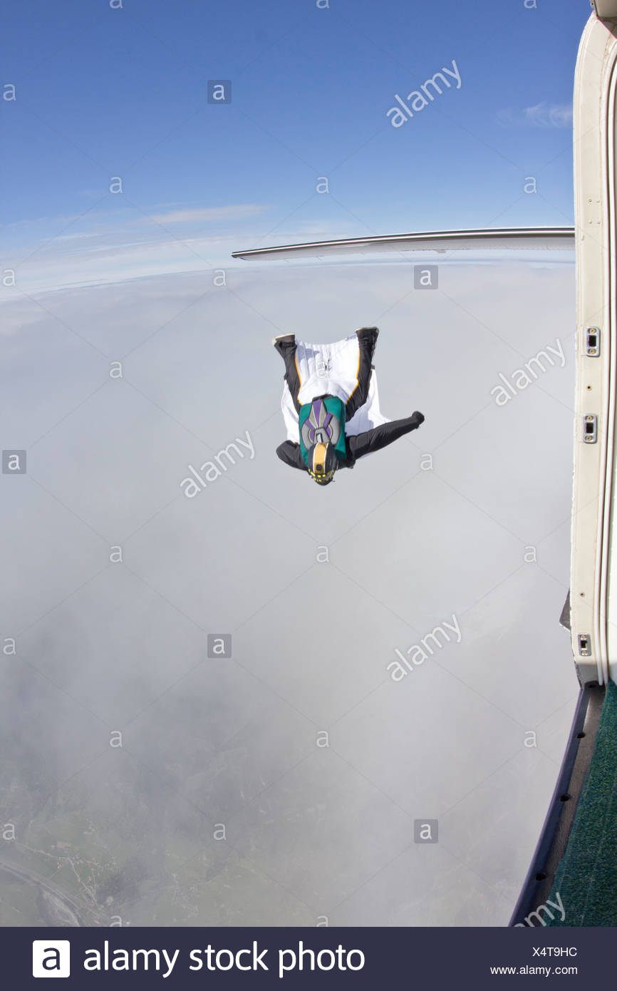 Mid adult man flying above clouds in wingsuit - Stock Image